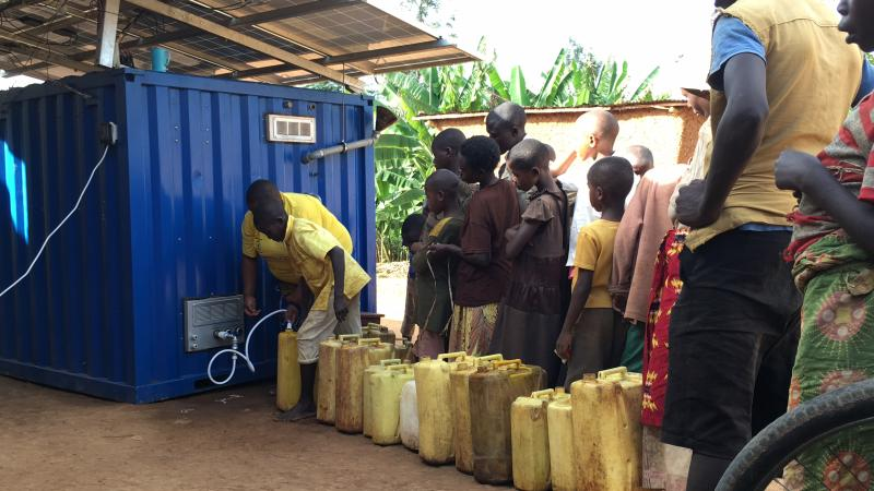 Children in Rwanda lining up to drink water from OffGridBox.